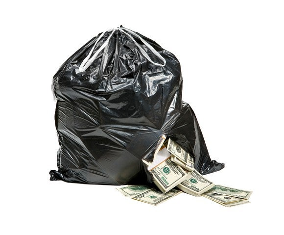 Cash spilling out of a ripped garbage bag