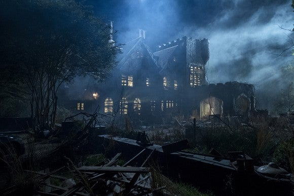 A Gothic house on a dark and cloudy moonlit night.