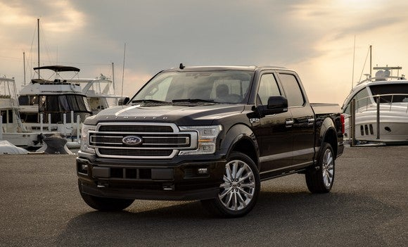 A black 2019 Ford F-150 Limited, an upscale full-size pickup truck, parked at a marina.