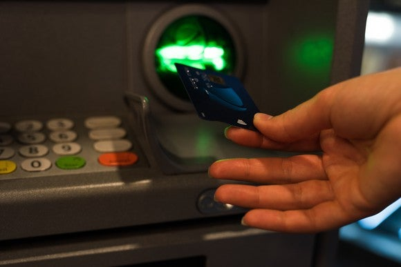 Close-up of woman inserting card into an ATM machine.