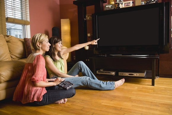 Two women sit on the floor of a living room, while one points to a large TV screen.