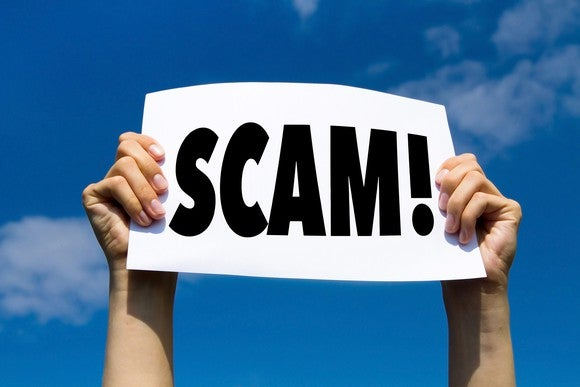 """Two hands are holding up a sign on which is printed the word """"scam"""" with an exclamation mark."""