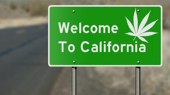 "A green highway sign that reads, ""Welcome to California,"" with a white cannabis leaf in the upper right-hand corner."