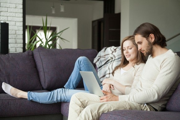 Young couple using laptop on a couch.