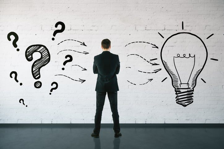A man, seen from behind, looks at a wall showing drawings of question marks to his left, with arrows pointing to a light bulb on his right.