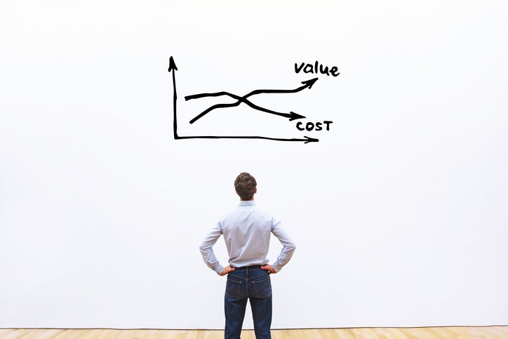 A man, seen from behind, stands with his hands on his hips as he looks at a chart showing two crossing arrows, one labeled value and the other labeled cost.