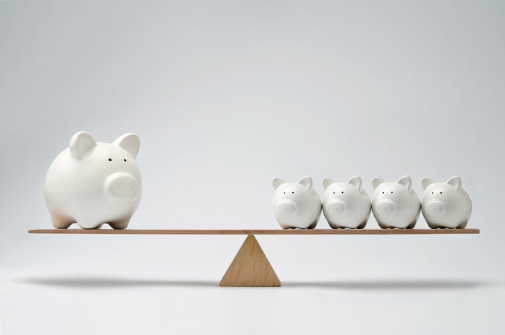 A balanced scale with one big piggy bank on one side and four smaller piggy banks on the other.
