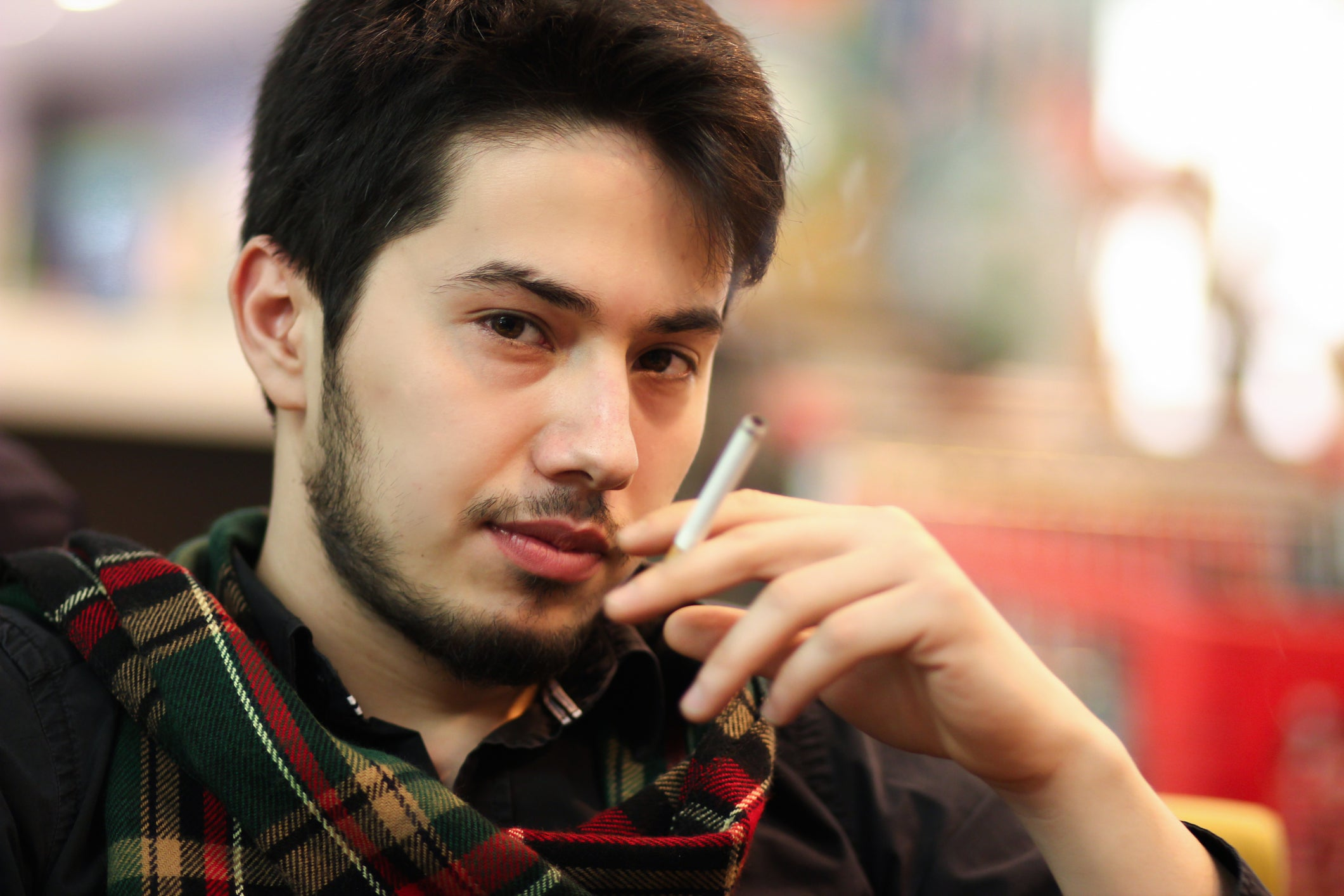A young man sitting down and smoking a cigarette.