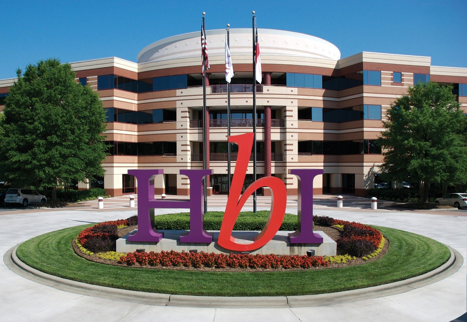 Office building with HBI logo in big letters in a median next to flagpoles.