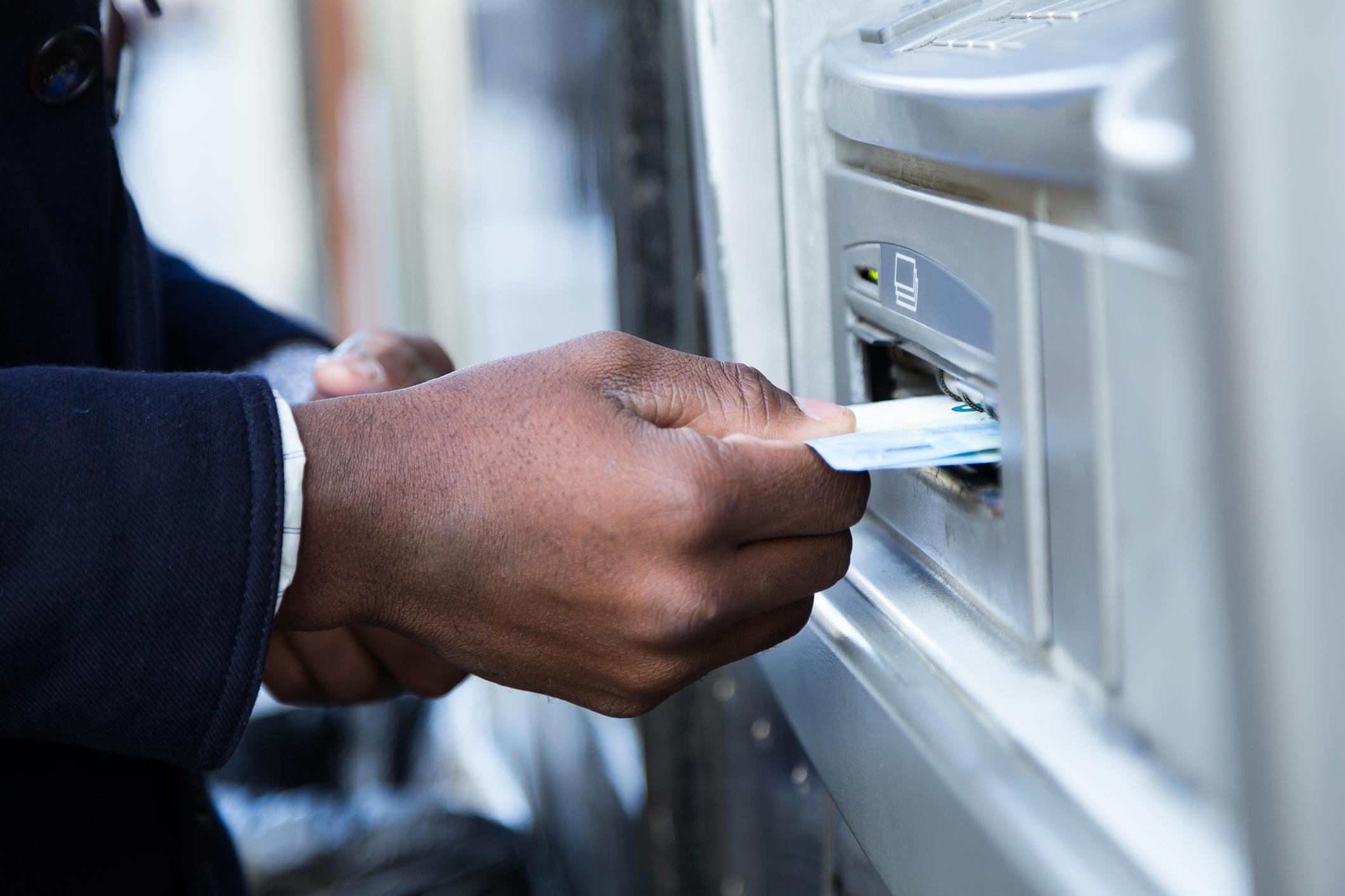 Person using ATM machine.