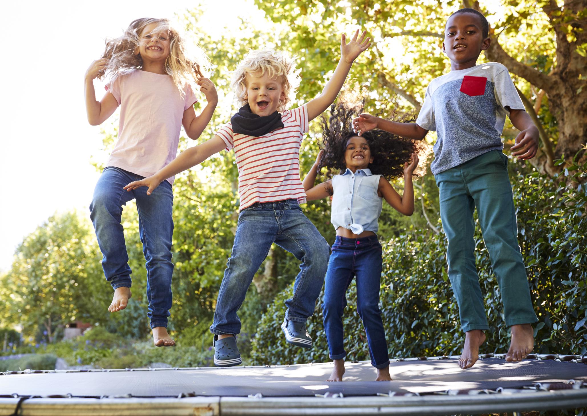 Four kids on a trampoline.