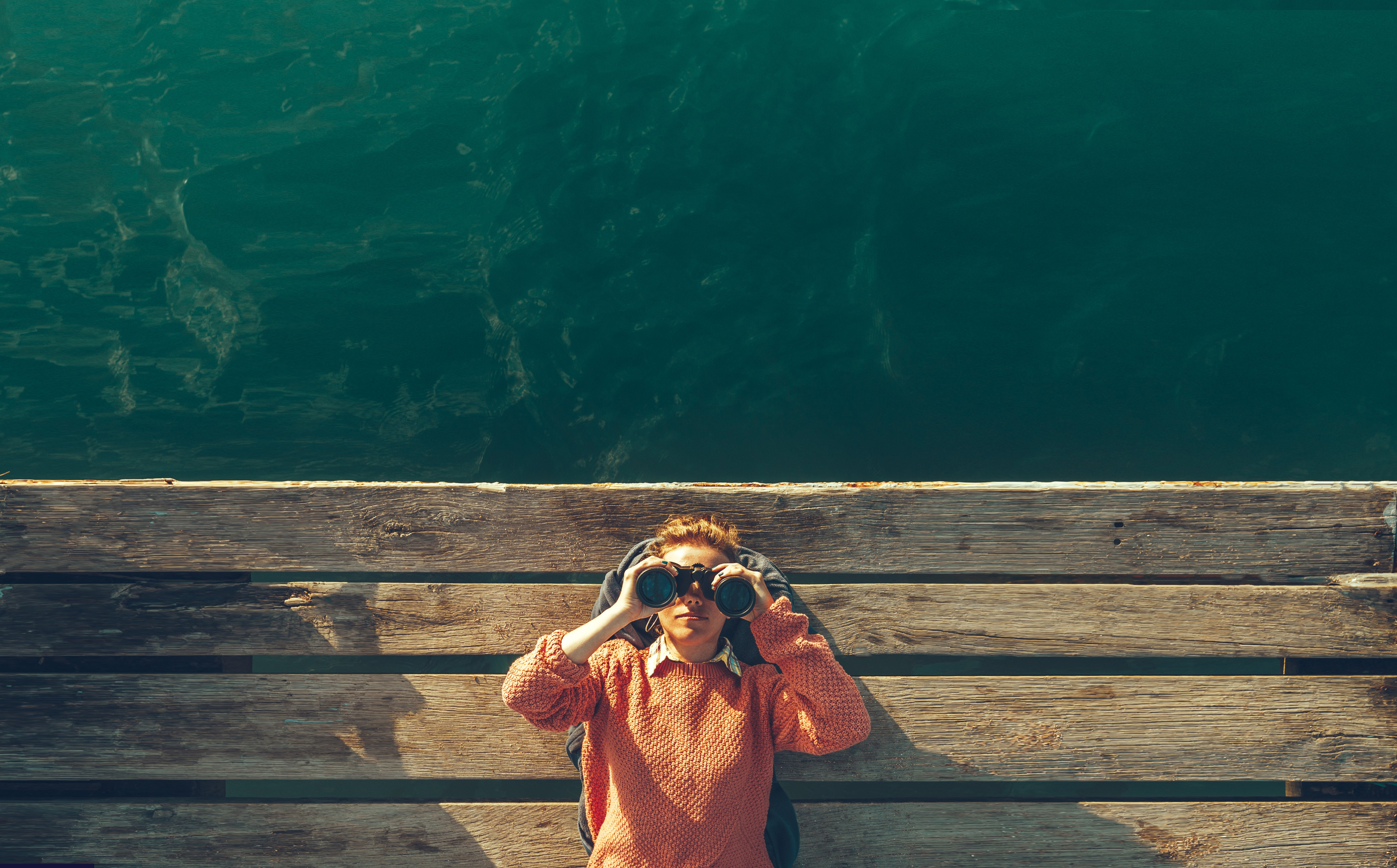A woman with binoculars on a dock