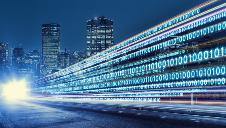 Binary digits (0s and 1s) flying above and along a highway leading into a city -- concept for digital transformation.