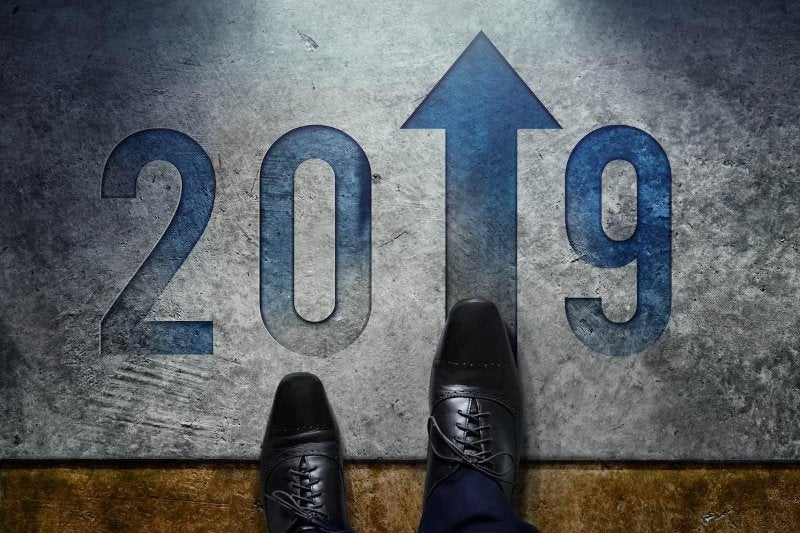 Someone walking on a 2019 floor mat where the one is an arrow pointing higher.