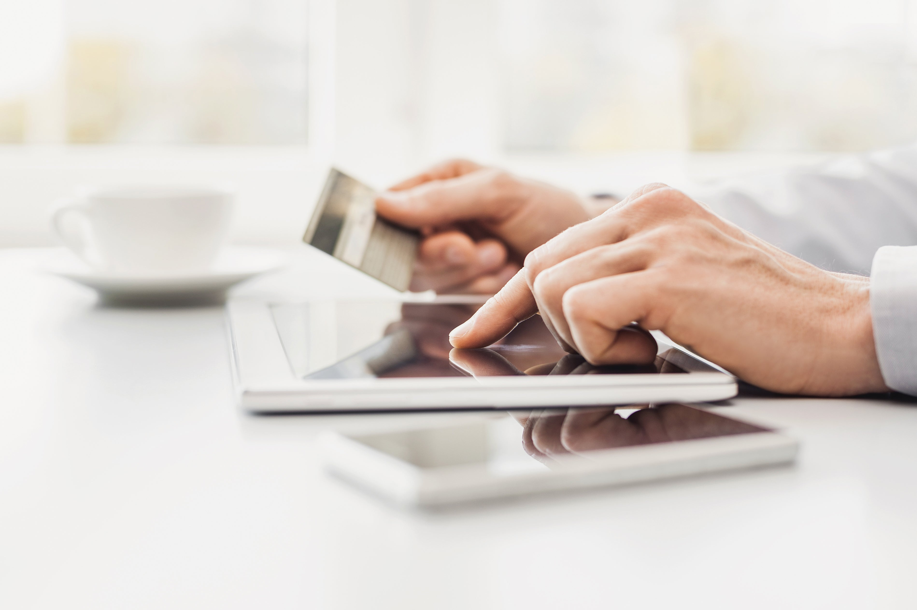 Person using a tablet and holding a credit card.