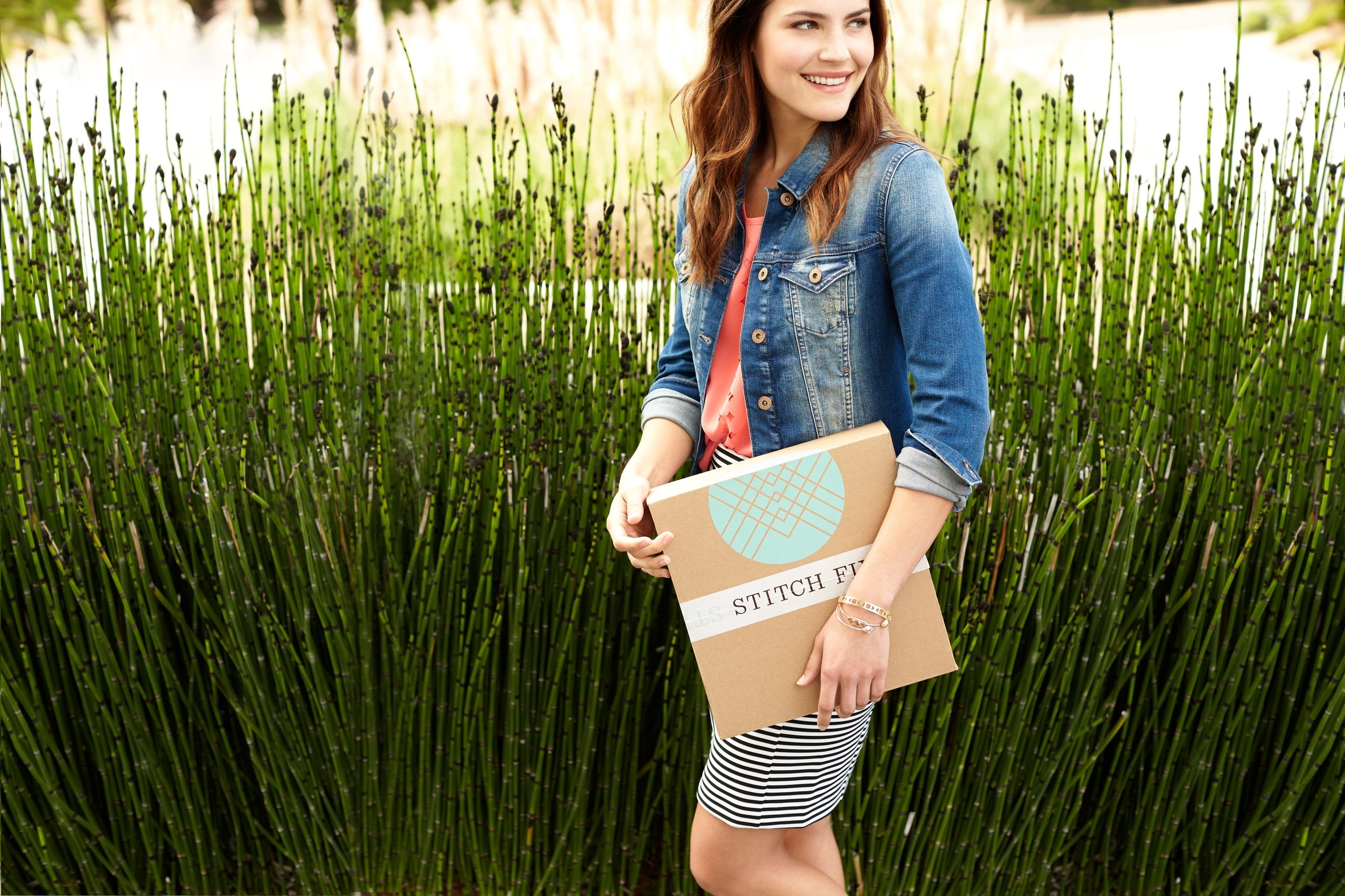 A smiling, fashionably dressed woman carrying a Stitch Fix box.