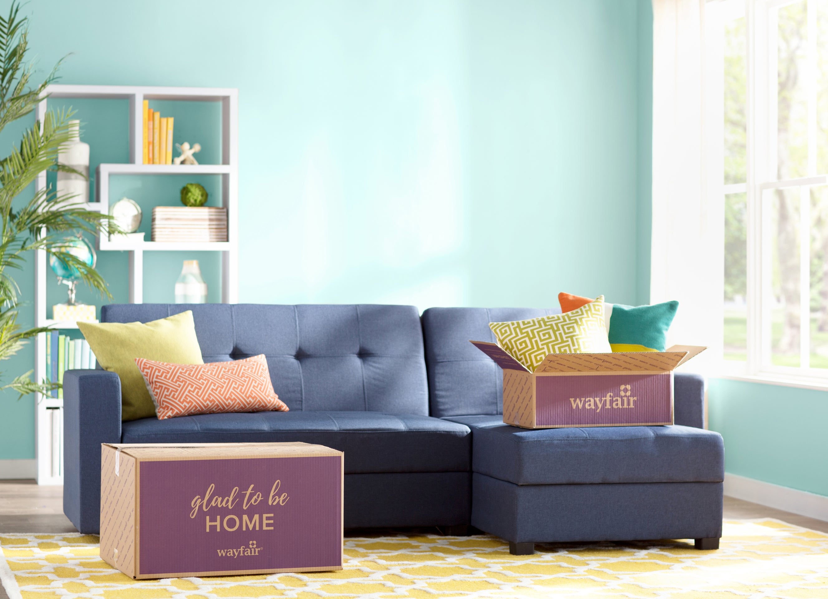 A living room with Wayfair boxes on the floor and couch.