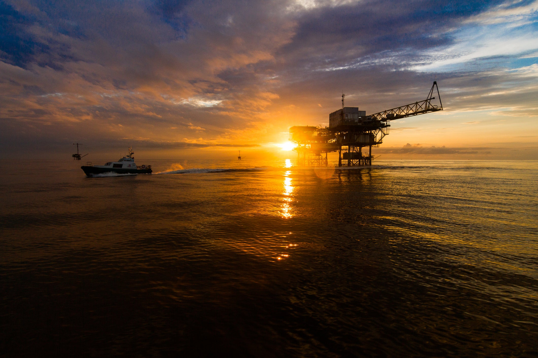 A ship near an offshore drilling rig at sunset.