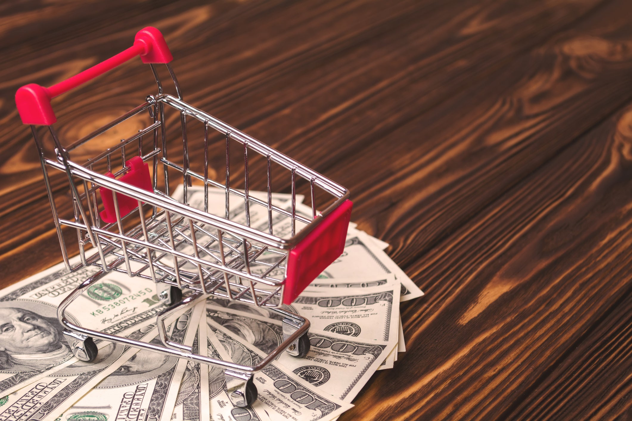 A miniature shopping cart with cash underneath standing on a wooden floor.