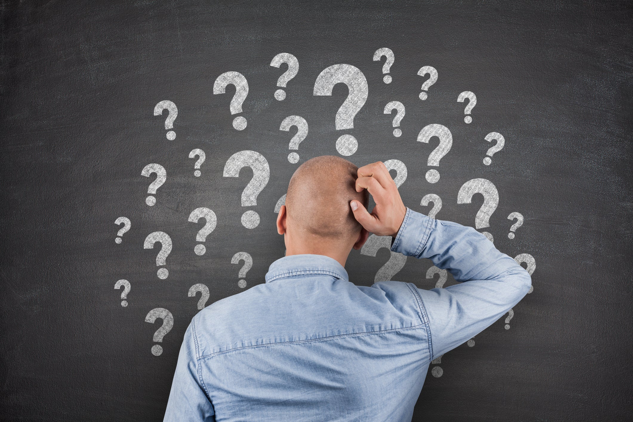 Bald guy scratching his head while looking at a chalkboard with lots of big question marks.