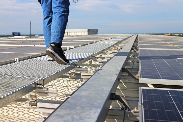 A man walking on a rooftop next to solar panels.
