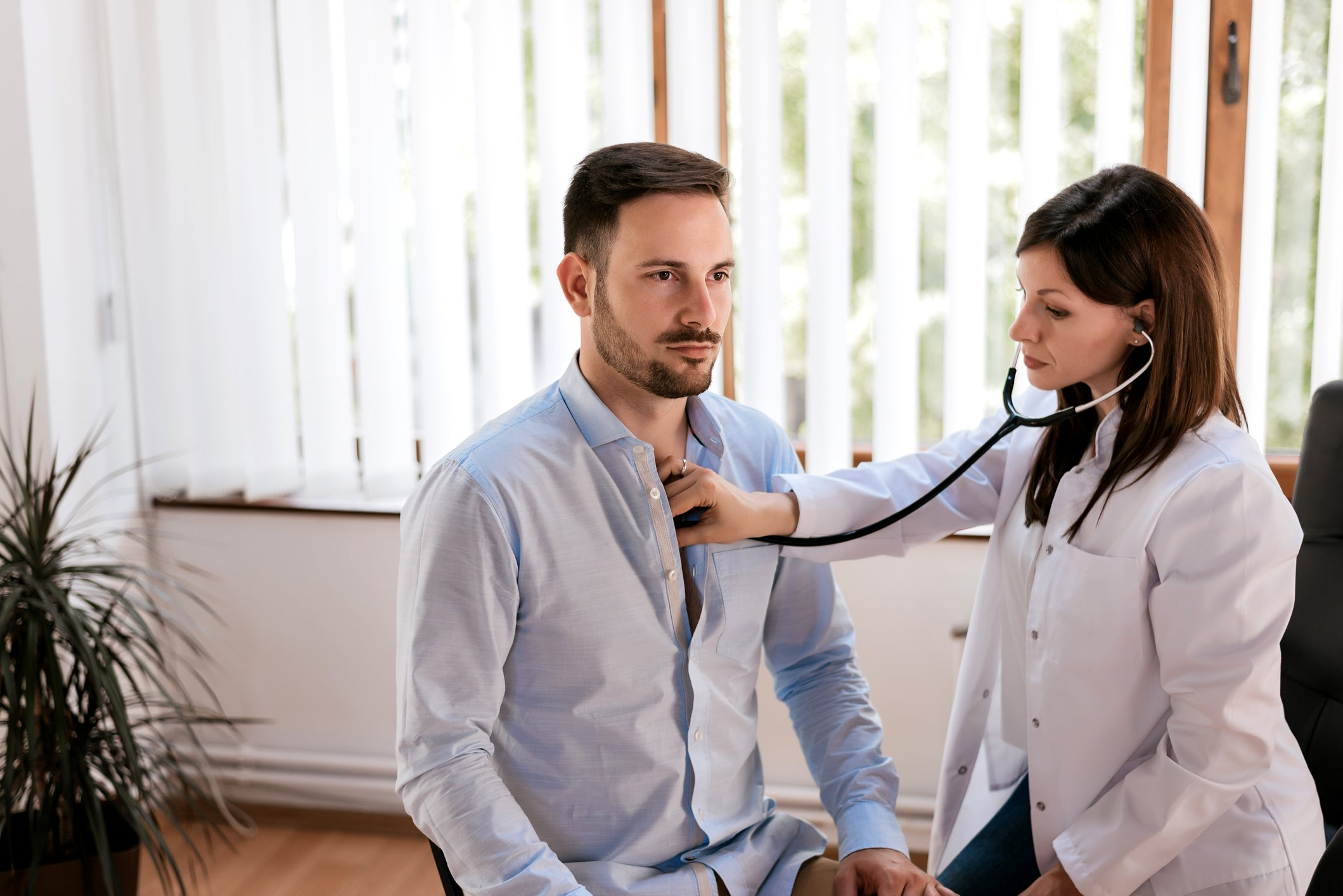 Female doctor with stethoscope on male patient's chest.