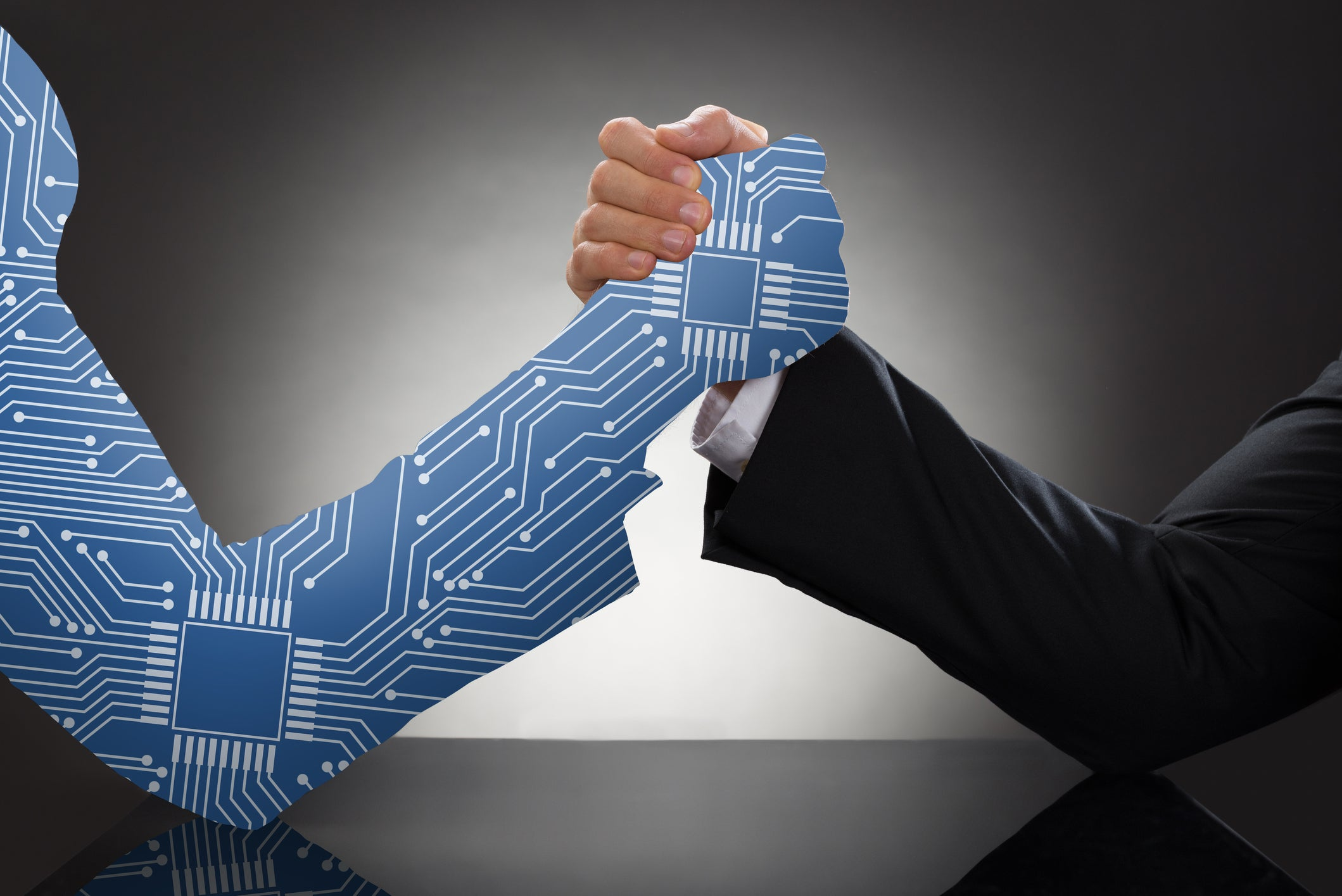 A man in a suit arm wrestles another arm made up of cartoon digital wiring.