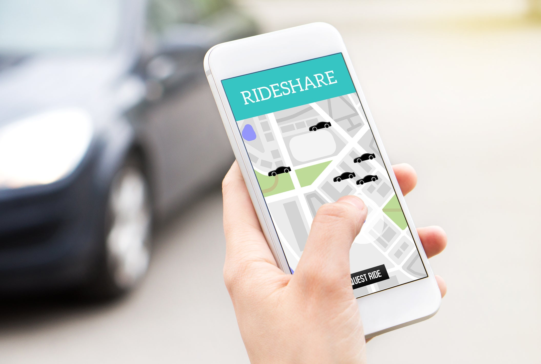 Person holding a smartphone with a ride-sharing app open.