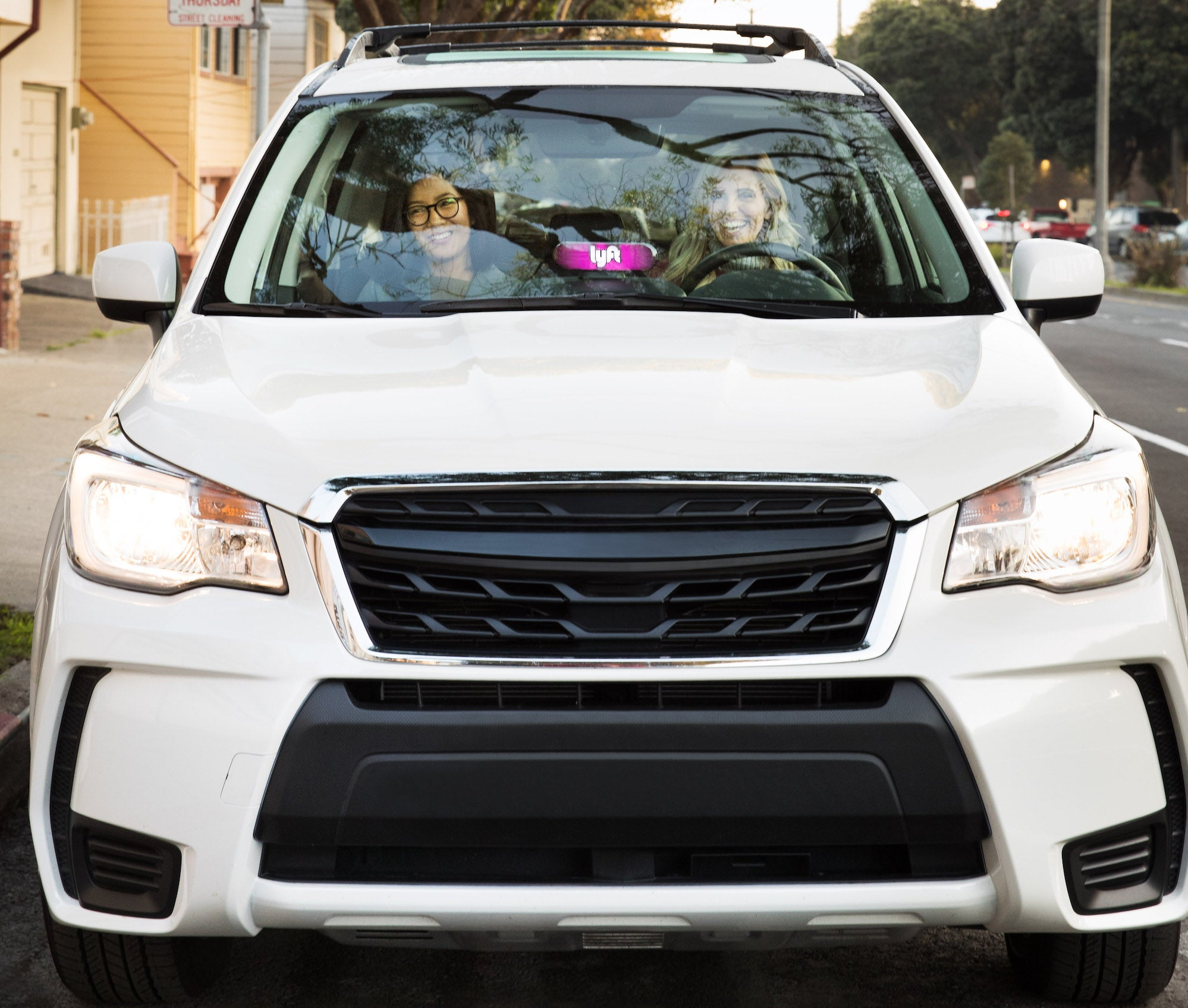 Two women sitting ina a white car.