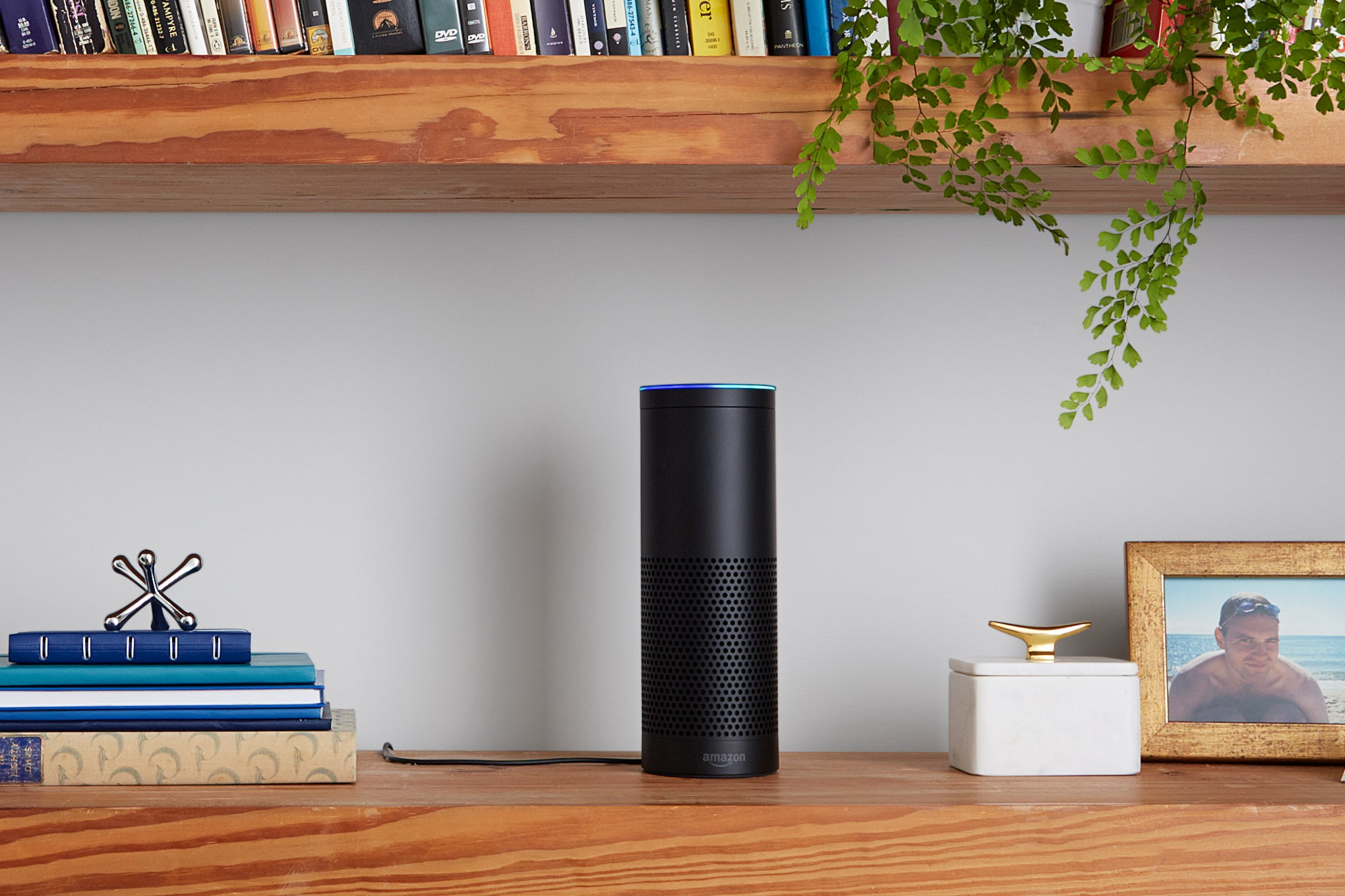 An Amazon Echo speaker on a bookshelf, next to a stack of books and a picture frame