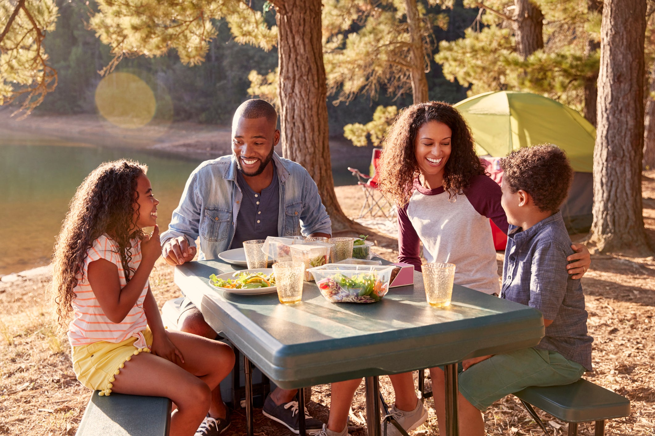 Man, woman, young girl, and young boy sitting at picnic table with food laid out on top of it.