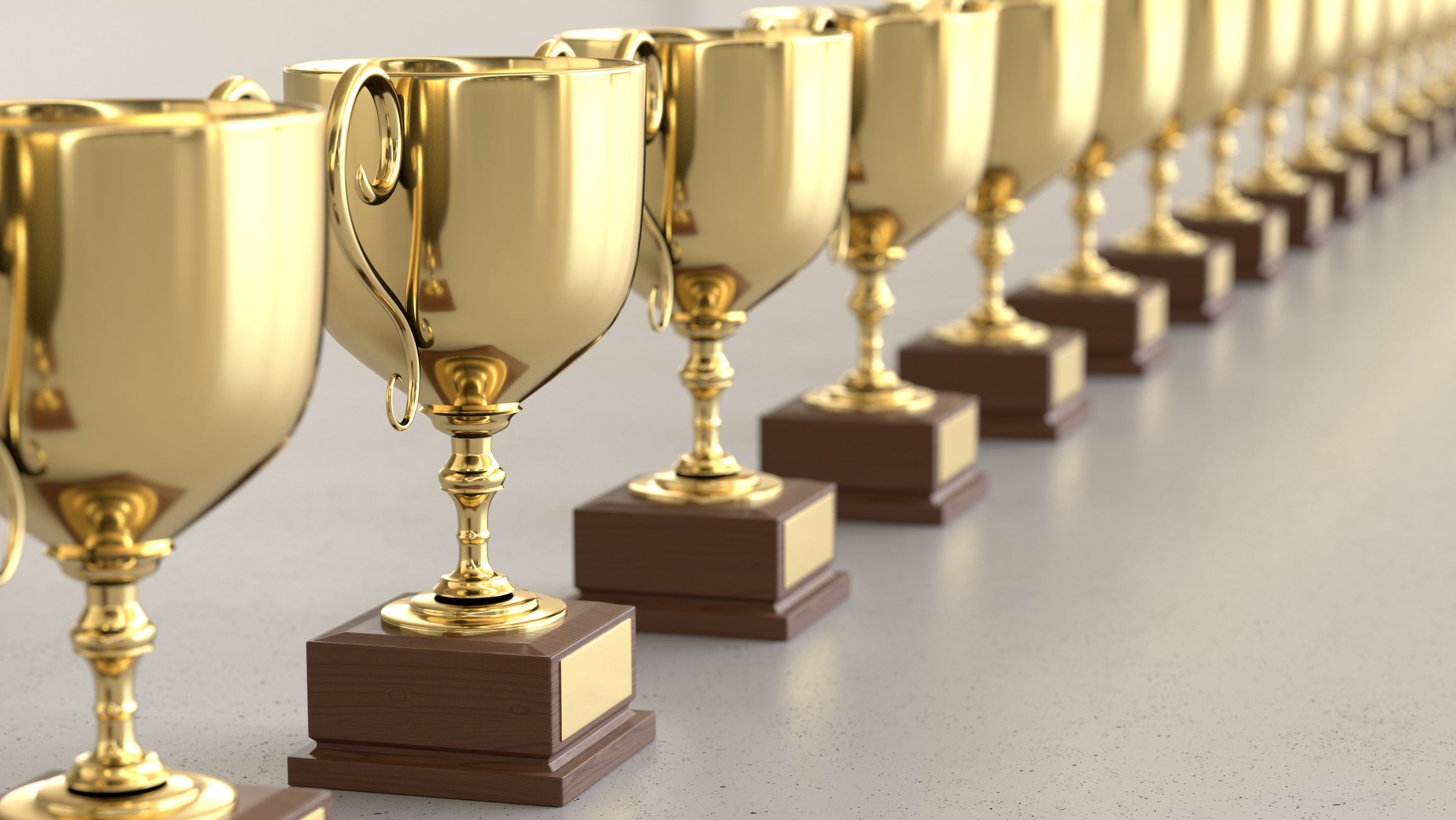 A row of gold trophies on a grey table.