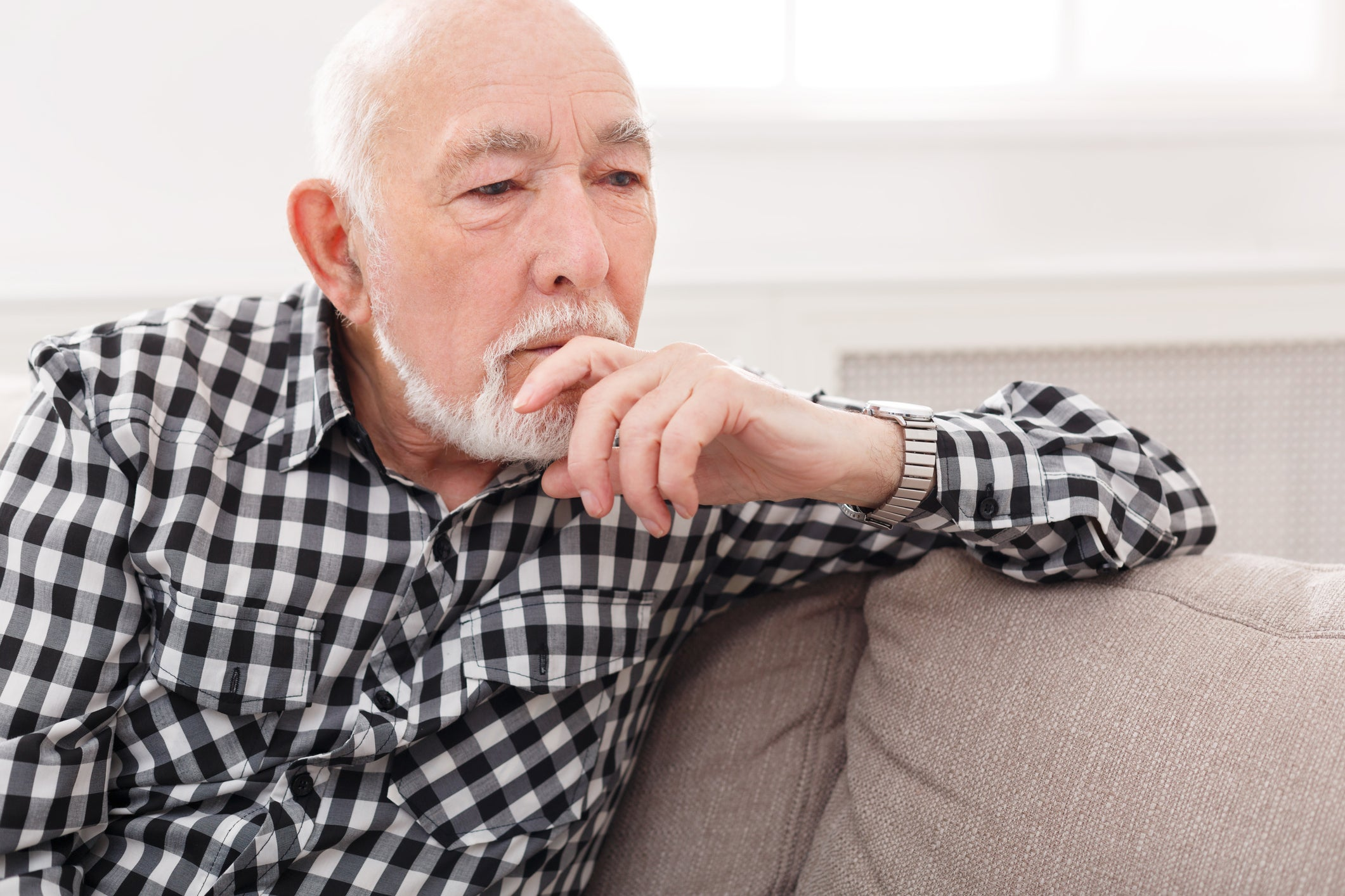 Older man sitting on couch, with hand resting on chin as if deep in thought.
