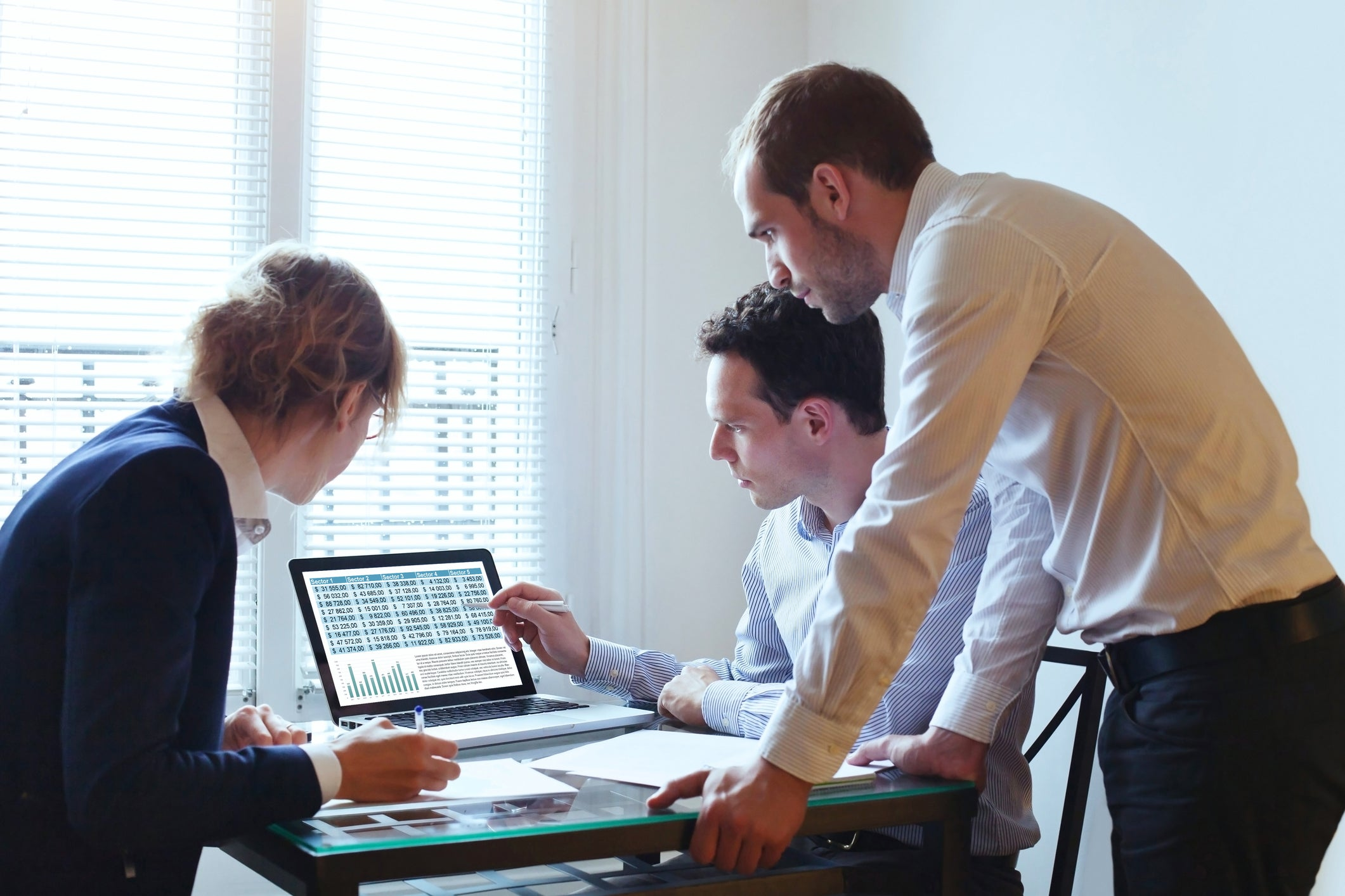 A group of three office workers gather around a computer displaying charts.