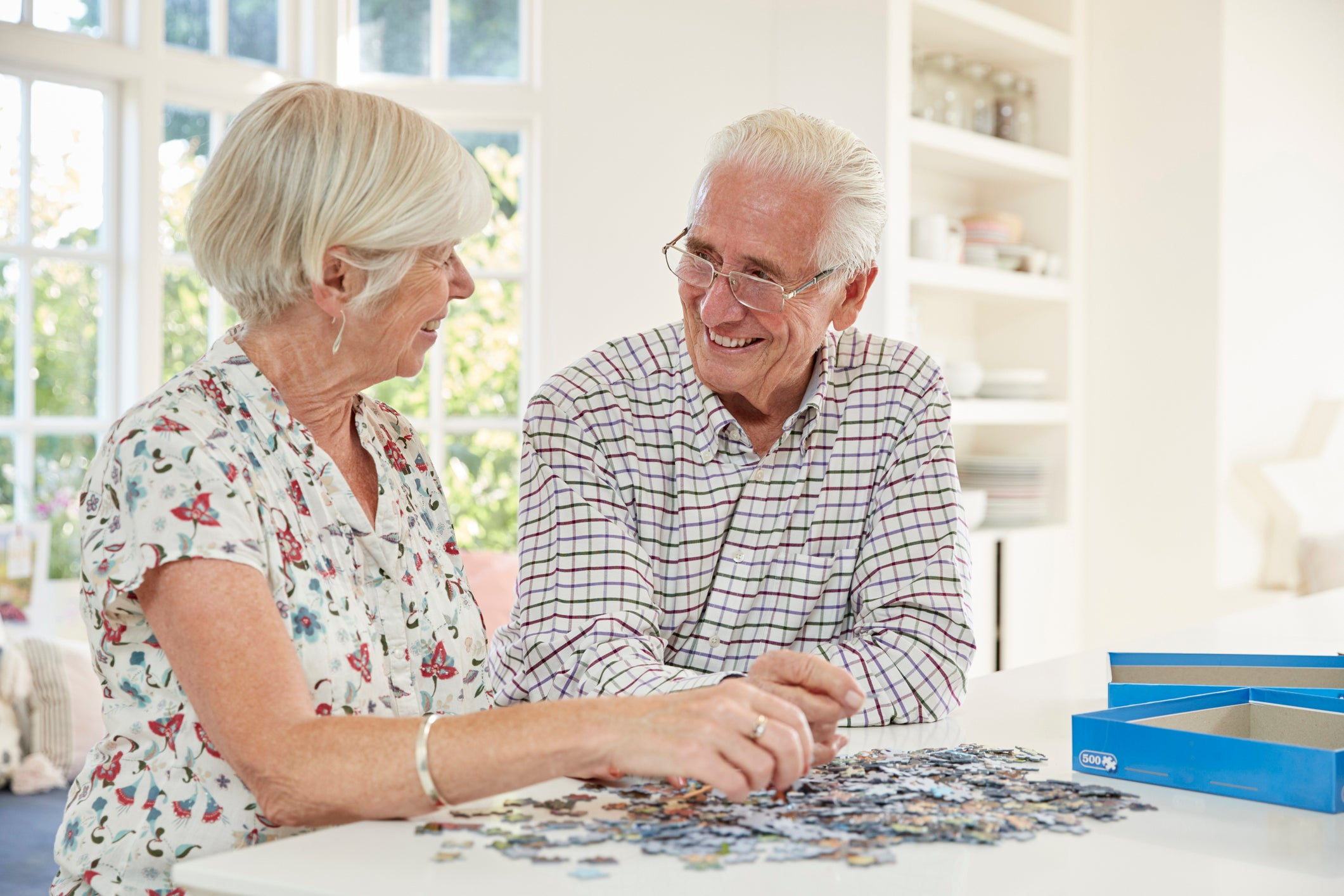 Senior couple seated at a table, doing a puzzle.