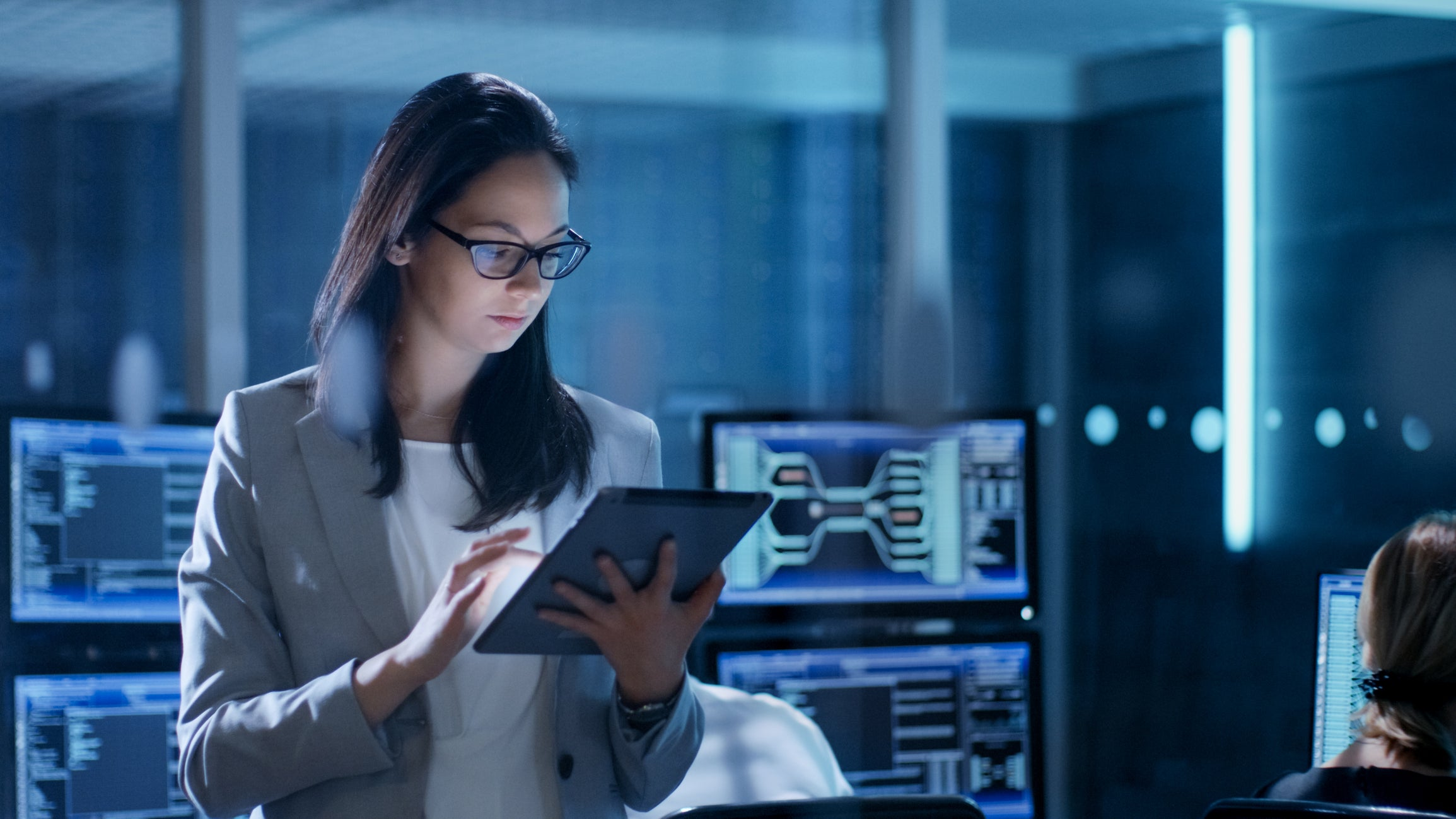 Woman in server room with tablet in her hand