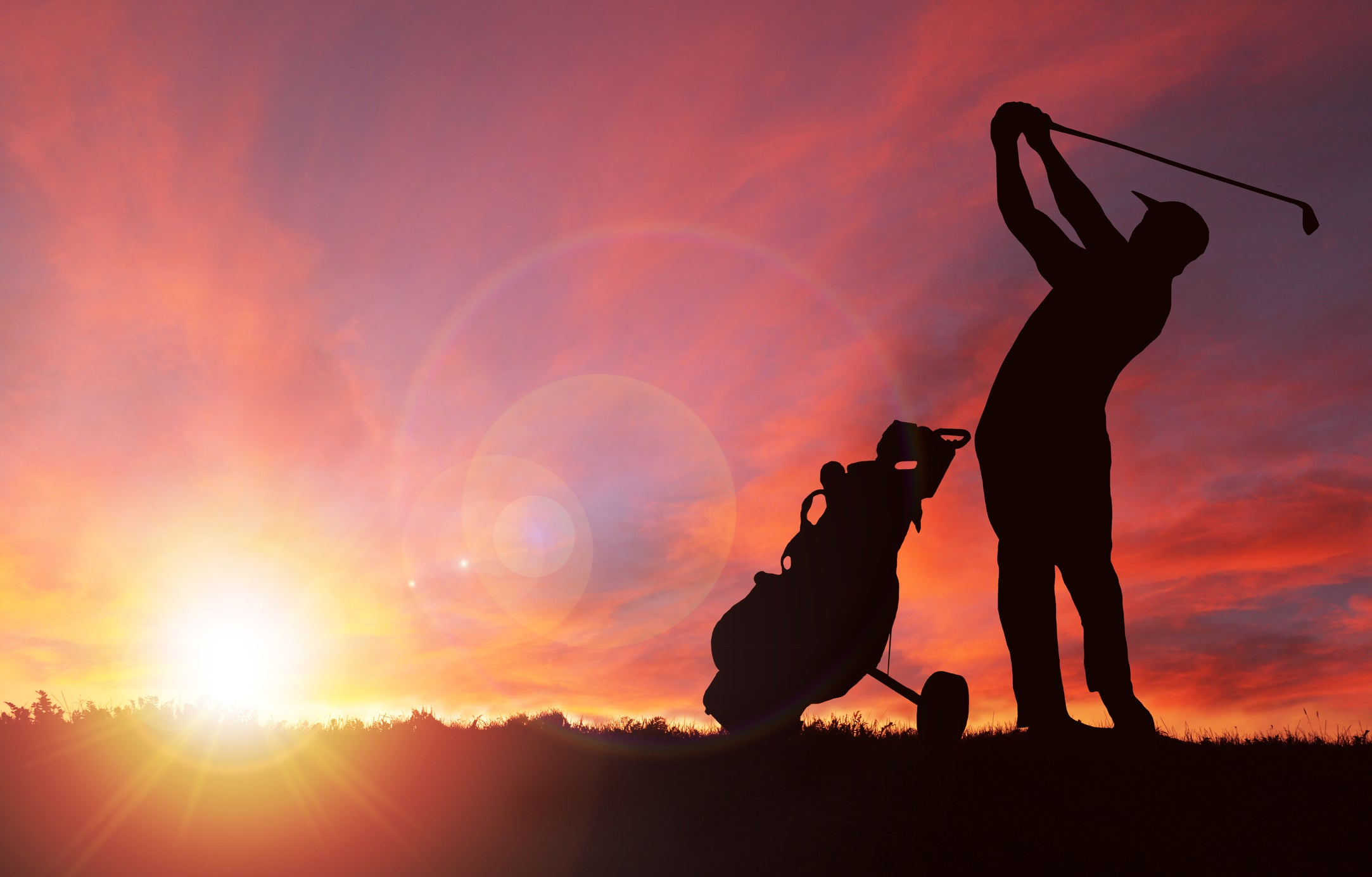 A golfer swings next to his bag at sunset.