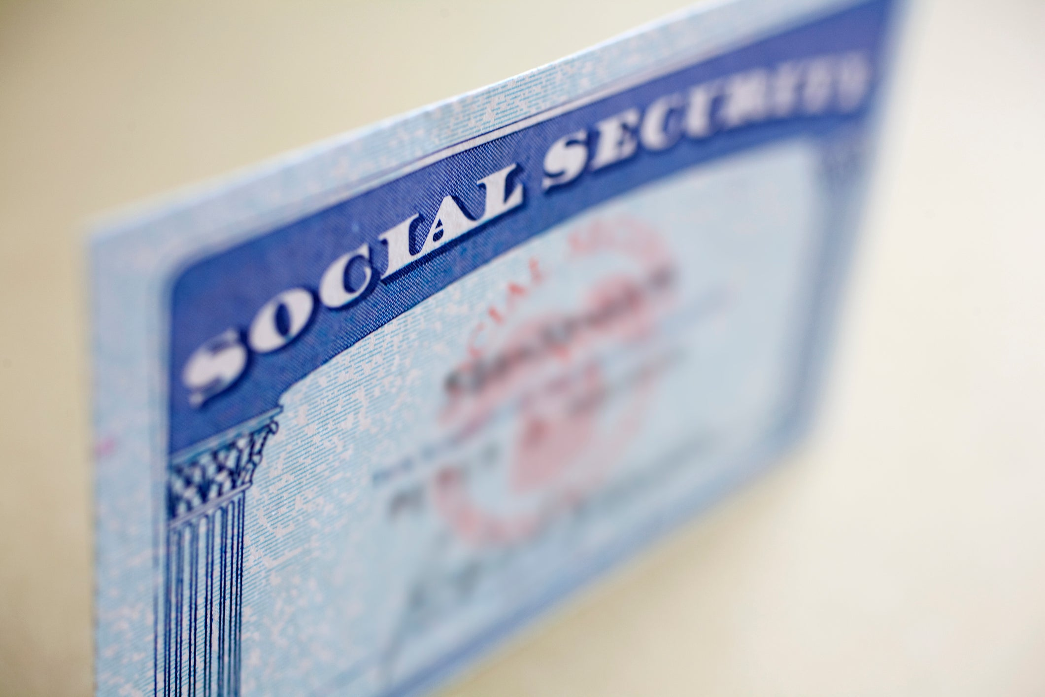 A Social Security card standing up on a table, with the name and number of the cardholder blurred out.