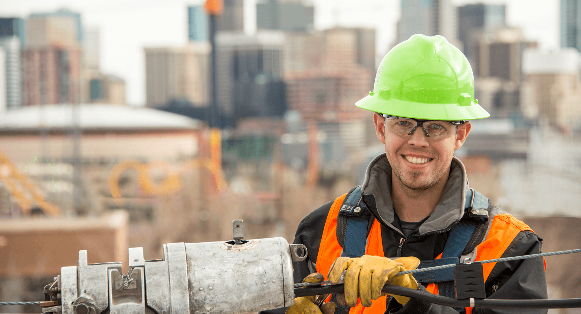 Smiling worker with green hard hat connecting telephone wire in front of a city skyline.