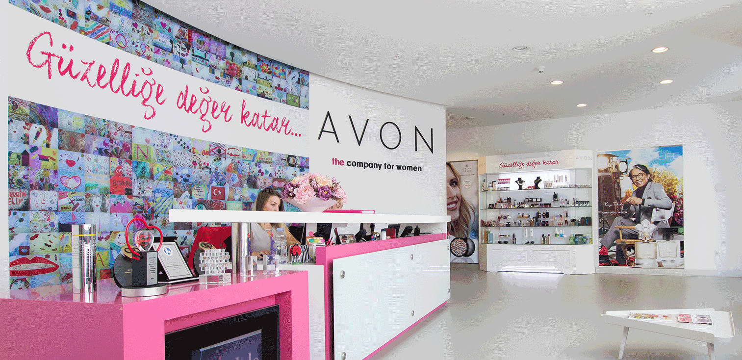 Office lobby with Avon logo on wall, with white and pink desk and various pictures and products.