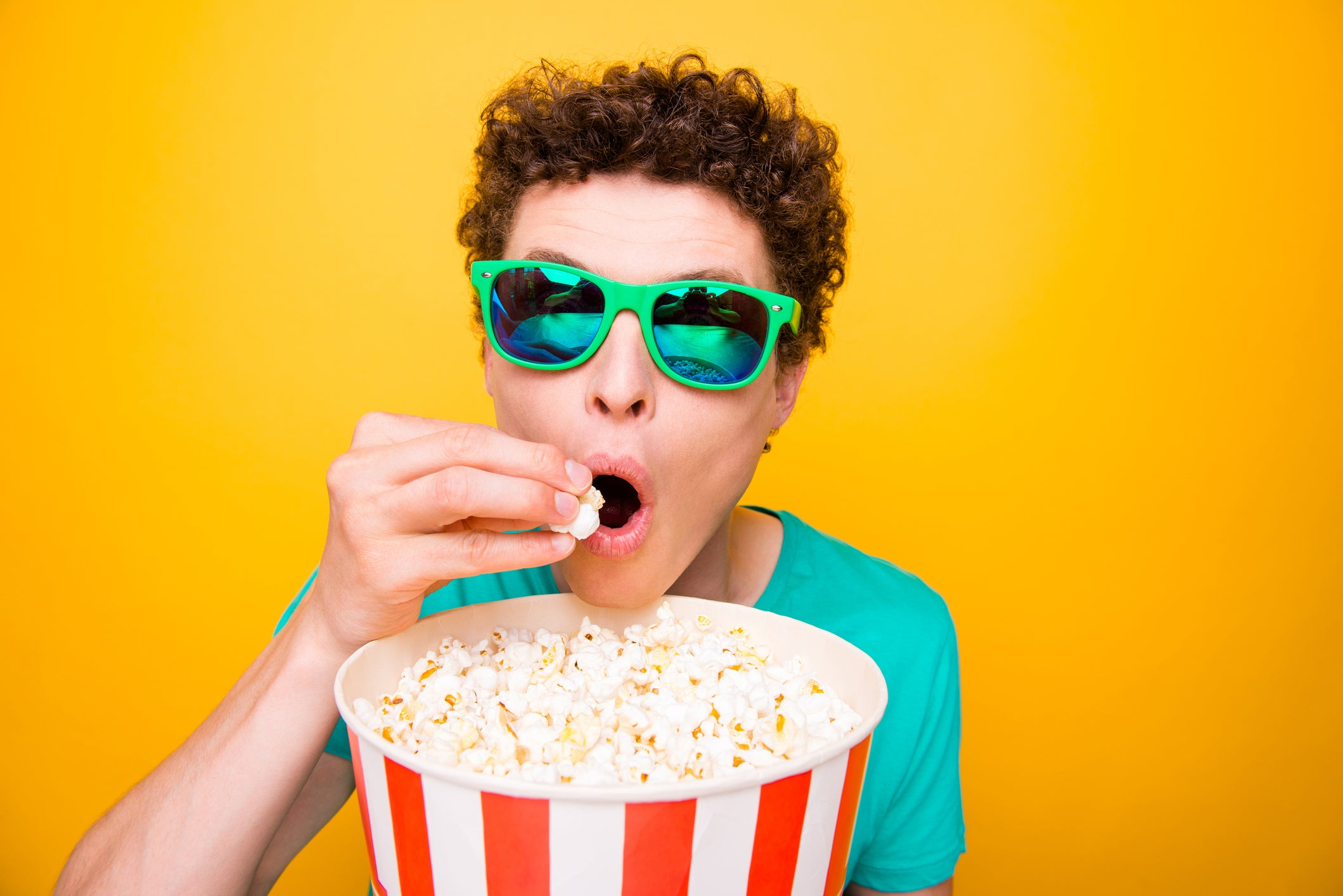 A male teenager in sunglasses wolfing down popcorn.