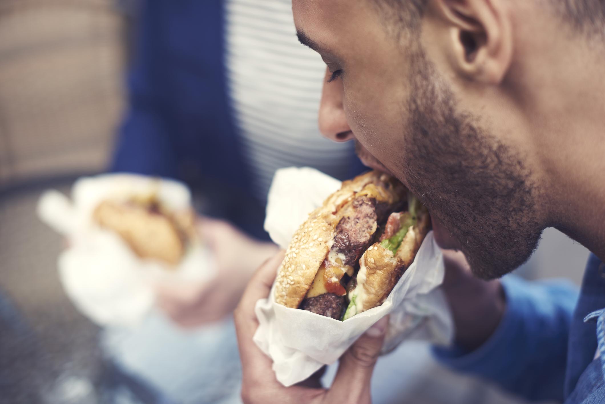 A man taking a bite of a cheeseburger.