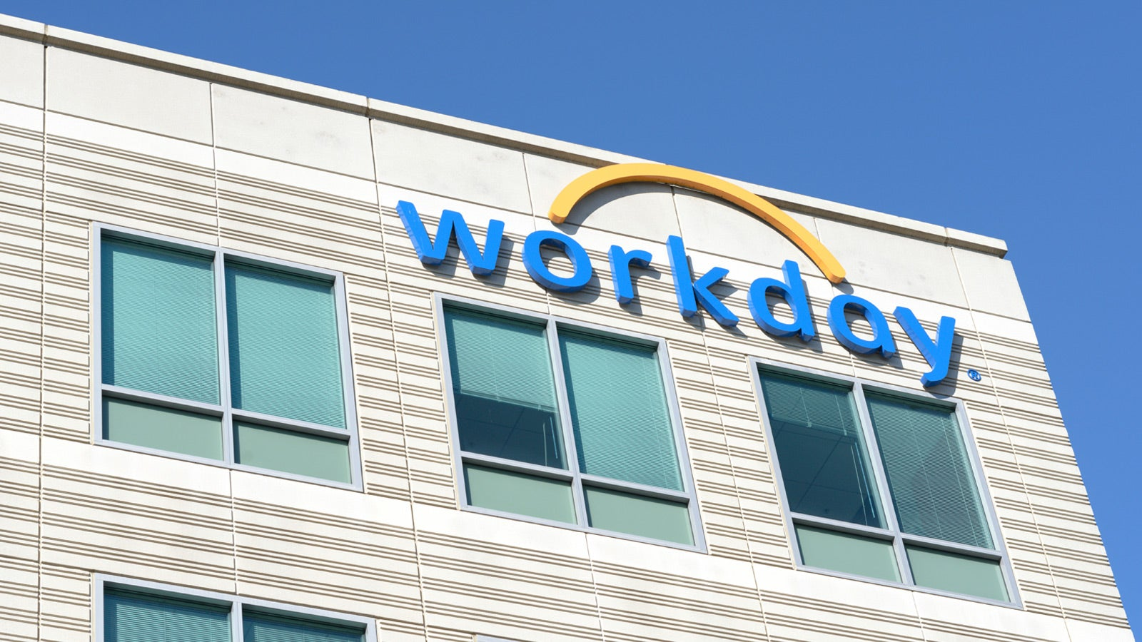 Workday office building with blue and yellow company logo on the side.