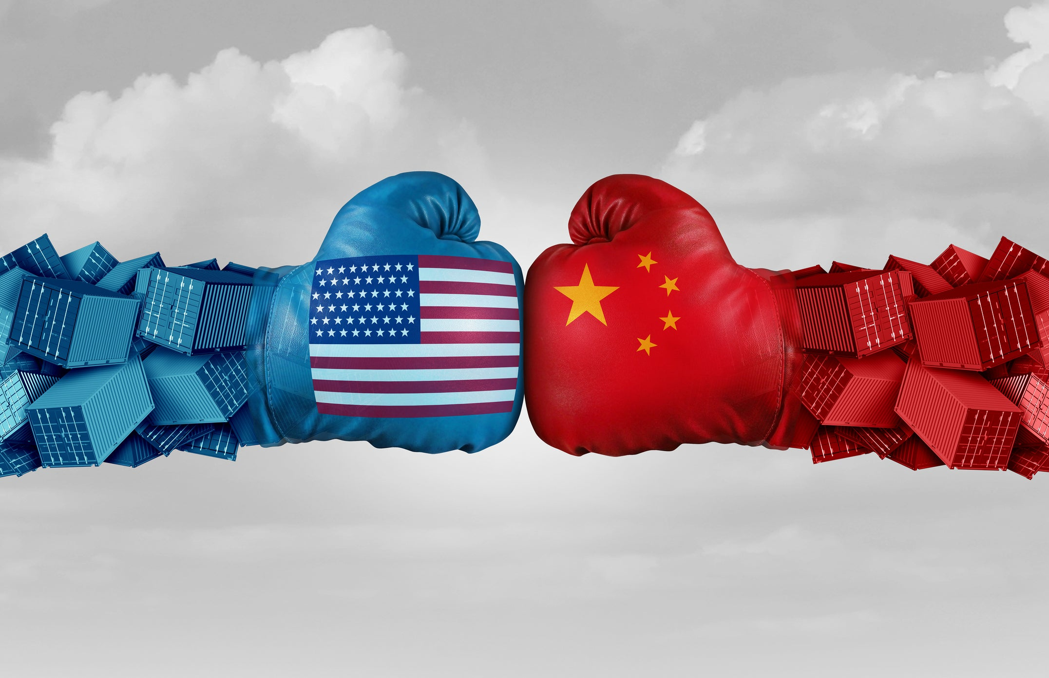 Two boxing gloves, one with the U.S. flag painted on it, one with the China flag painted on it, touch.