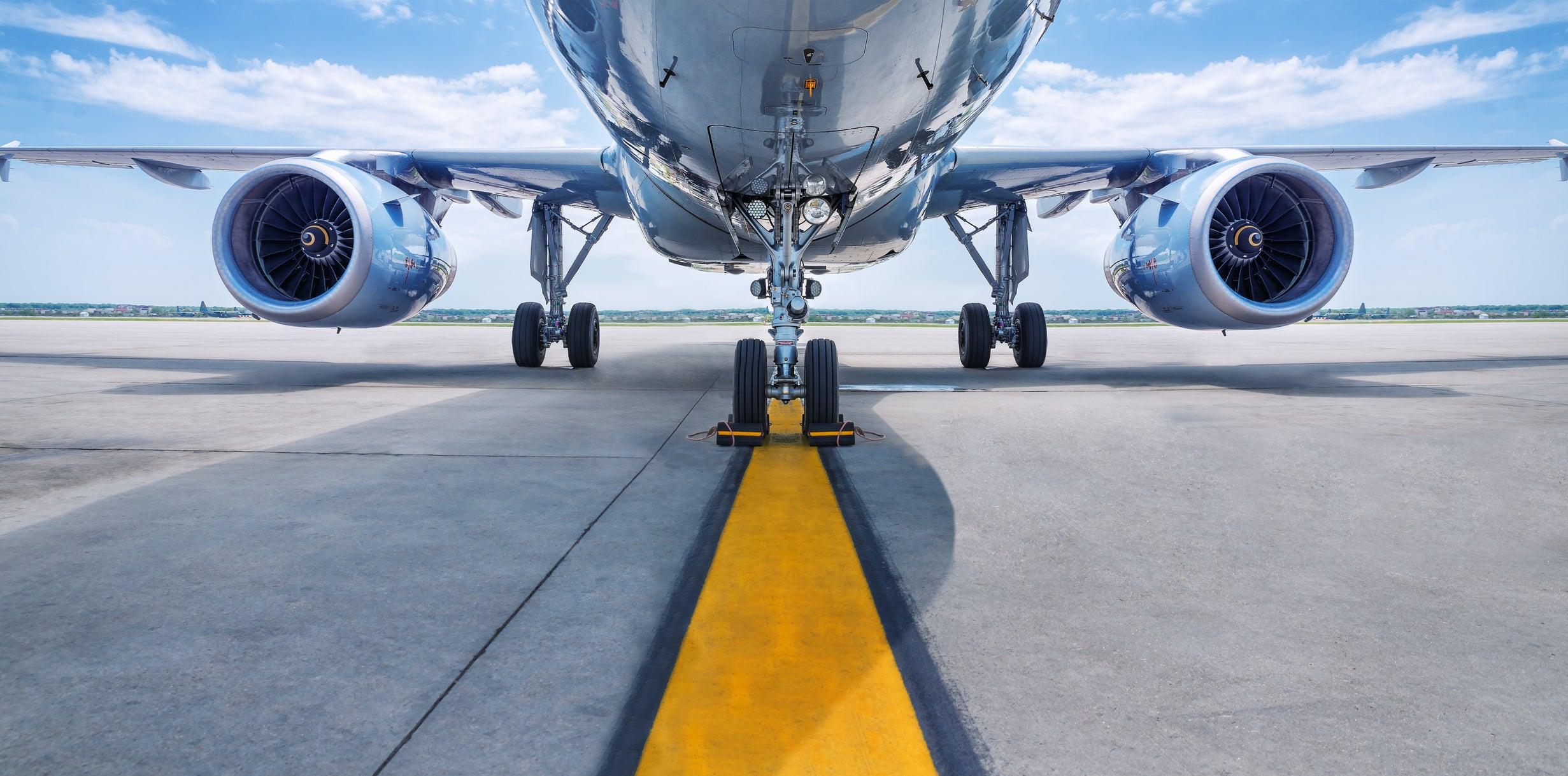 The bottom of an airliner on a runway.