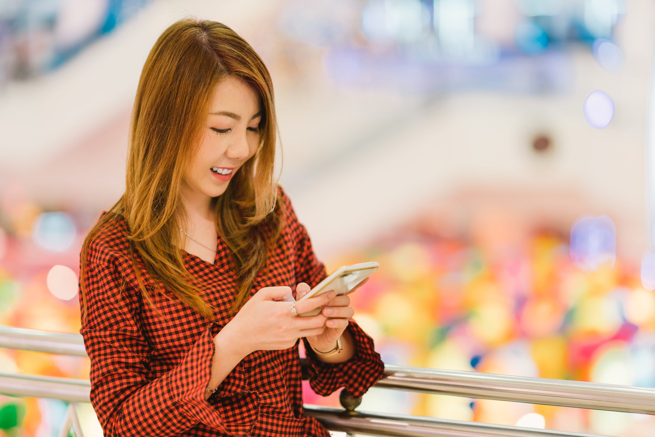 A smiling Asian woman looking at a smartphone
