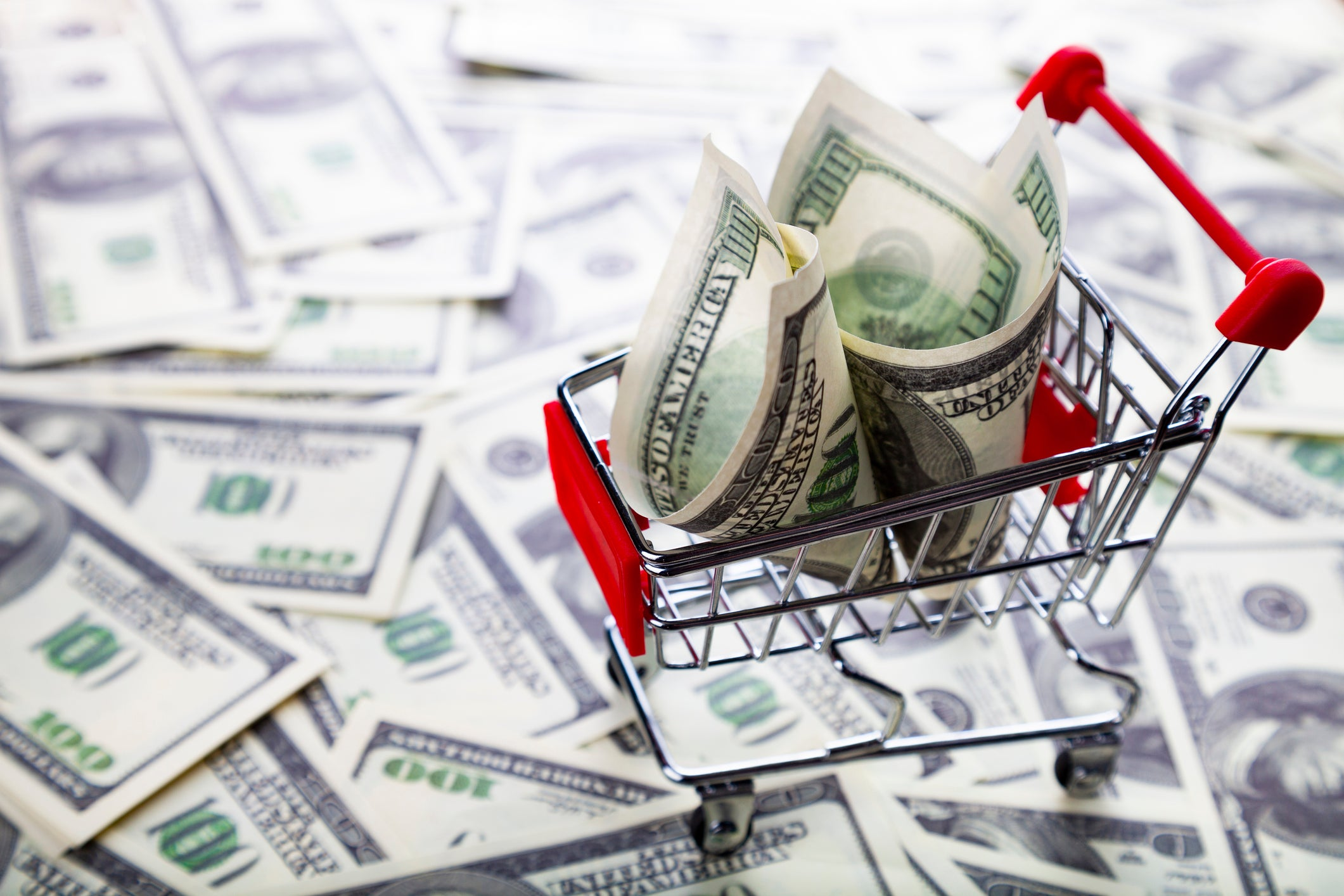 Tiny shopping cart with a $100 bill in it on top of a pile of $100 bills