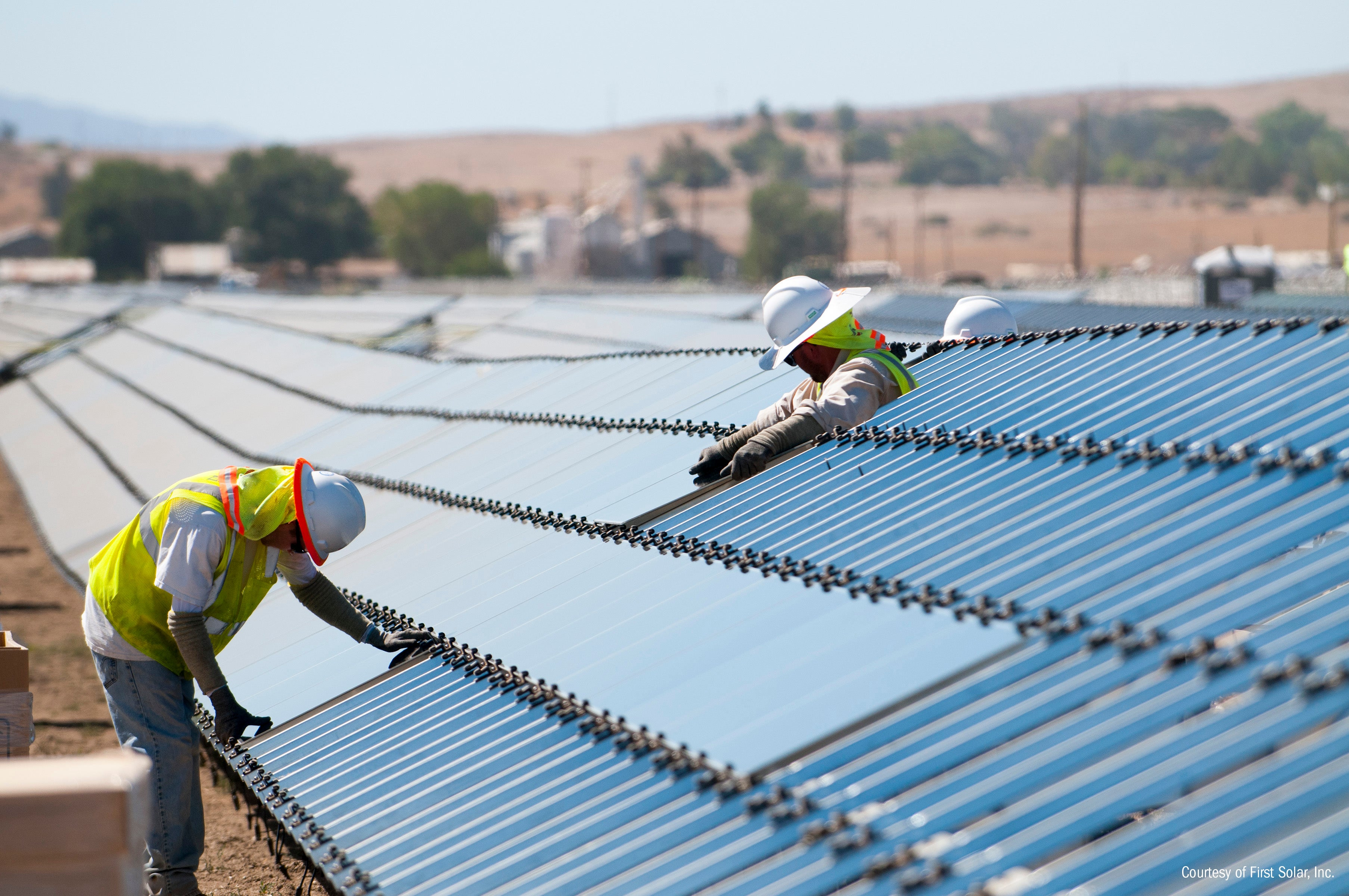 Two workers working on a First Solar power plant that's under construction.