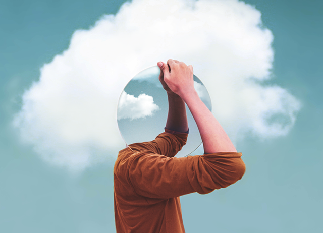 A person holding a reflective sphere where their head should be with a cloud in the background.