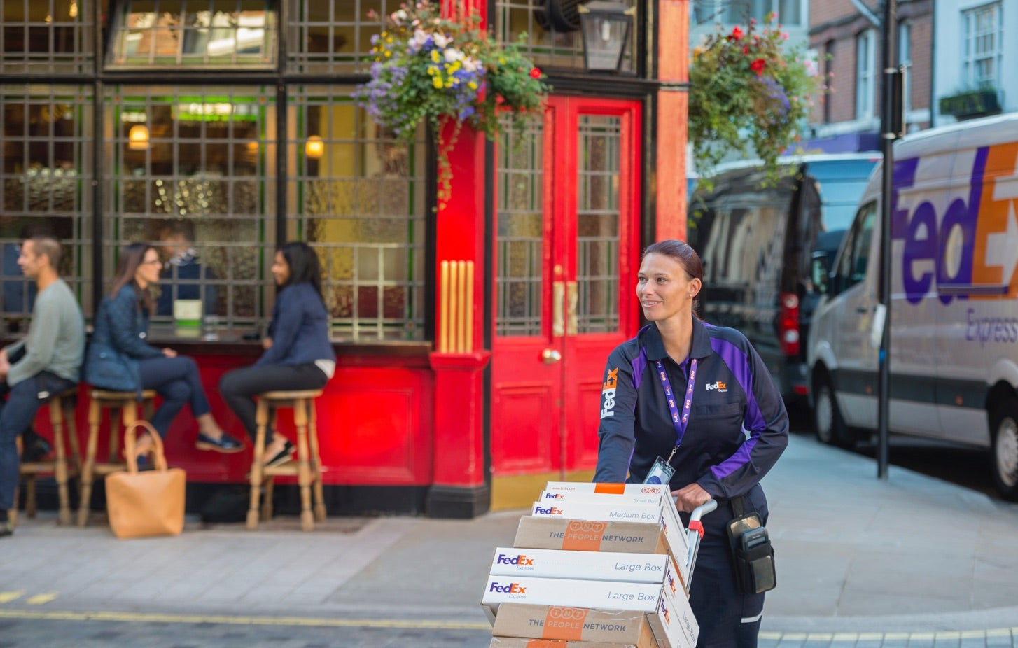 Female FedEx driver delivering packages in front of a restaurant with outdoor seating.